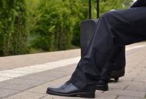 Geschäftsreisender mit Koffer auf leerem Bahnsteig