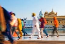 Flanierende Menschen vor indischem Tempel