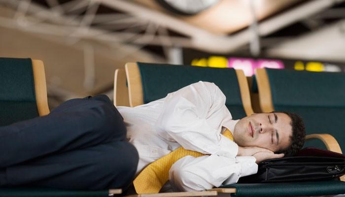 Geschäftsmann schläft auf Sitzbank am Flughafen