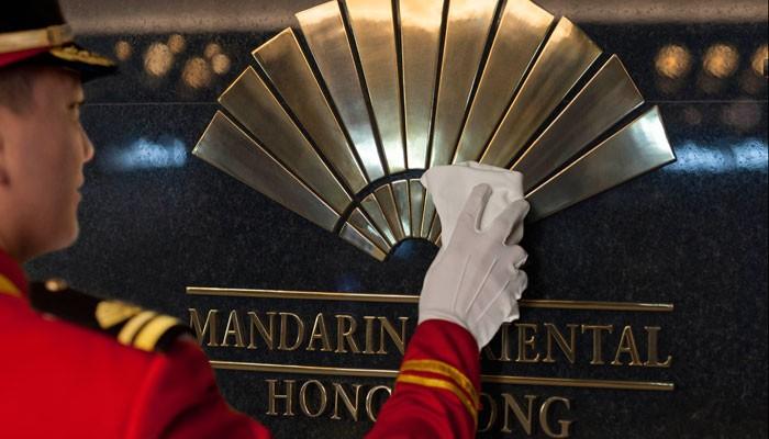 Page putzt Schild des Mandarin Oriental Hong Kong
