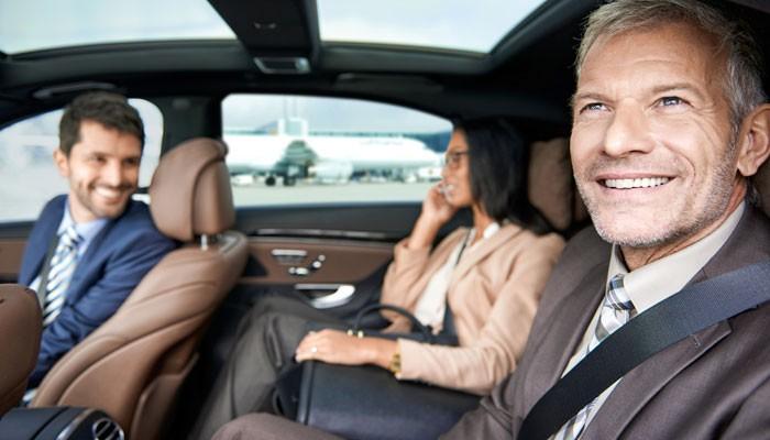 Zwei Geschäftsreisende und ein Fahrer in der Limousine