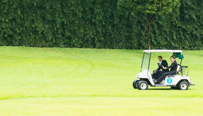 Zwei Geschäftsmänner im Golf Car