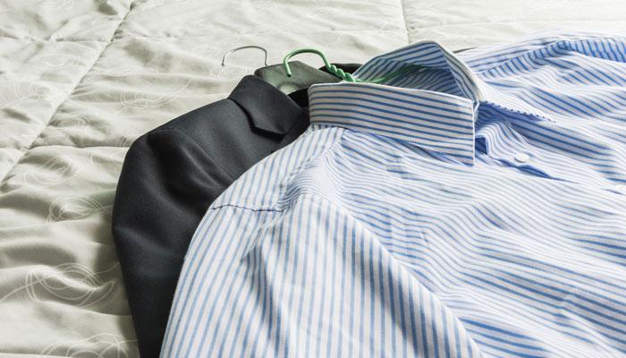 Anzug und Hemd auf Hotelbett