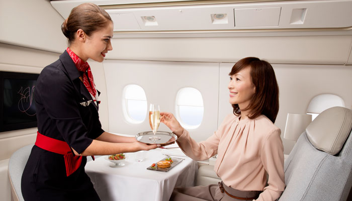 Flugbegleiterin Air France reicht Passagierin Champagner