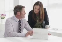 Mann und Frau im Büro vor einem Tablet
