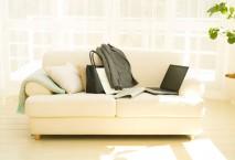 Laptop und Anzugjacke auf Sofa