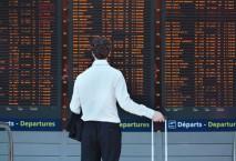Geschäftsmann vor Anzeigentafel am Flughafen