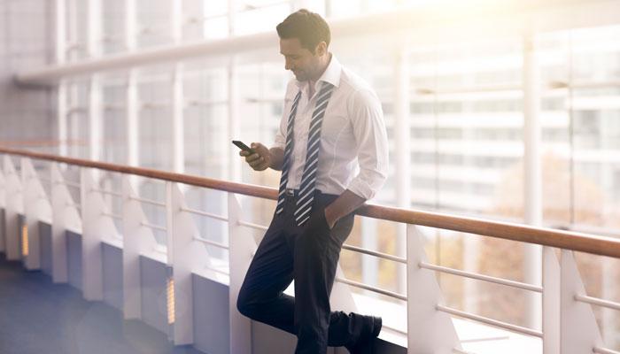 Geschäftsmann mit Smartphone vor Fensterwand
