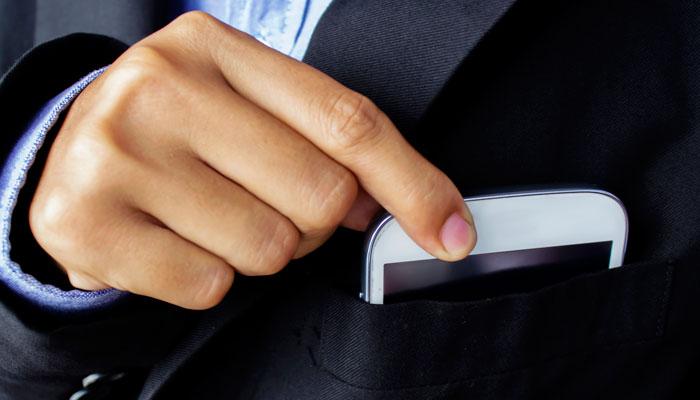 Geschäftsmann steckt Smartphone in Sakkotasche