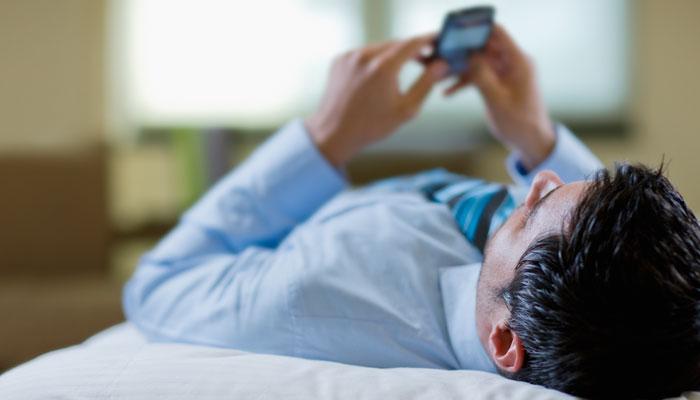 Geschäftsmann liegt mit Handy auf Bett