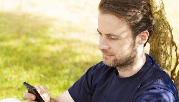 Mann mit Handy unter schattigem Baum
