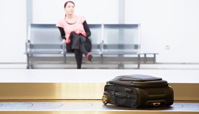 Frau wartet vor Gepäckband auf Koffer