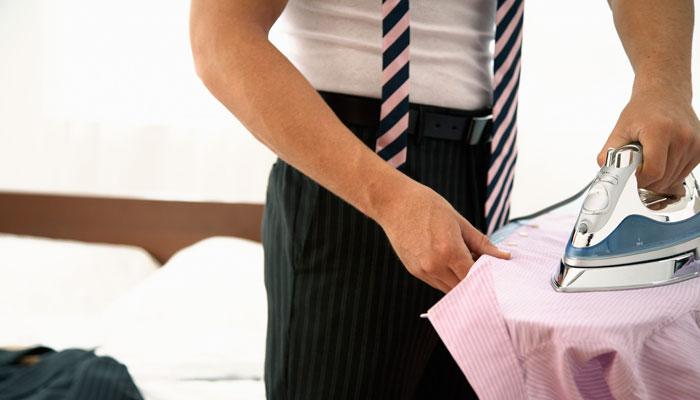 Geschäftsmann bügelt Hemd