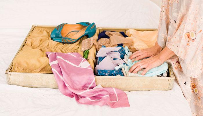 Frau packt Seidenschal in einen Koffer