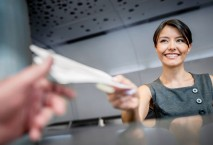 Dame hinter Airline-Schalter händigt Bordkarten aus