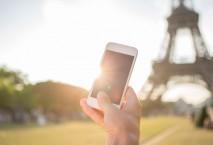 Hand mit Smartphone vor Eiffelturm