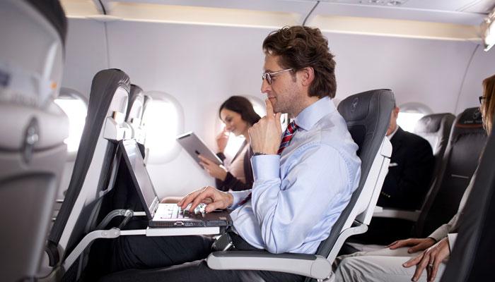 Mann mit Notebook in Lufthansa-Kabine