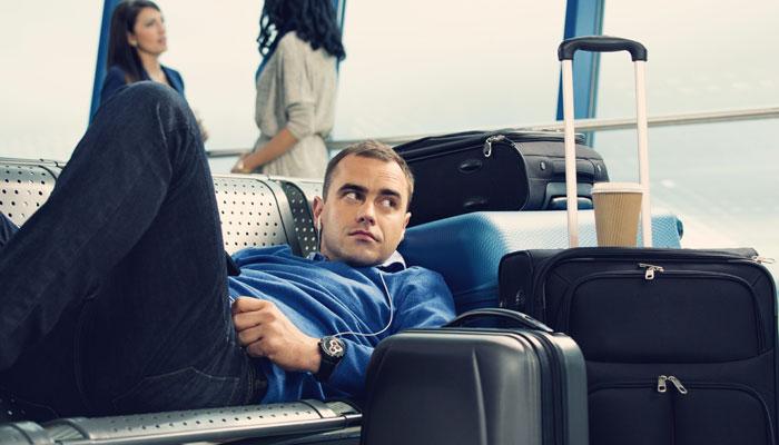Fluggast liegt auf Bank in Flughafengebäude