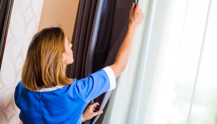 Zimmermädchen zieht Gardine zu