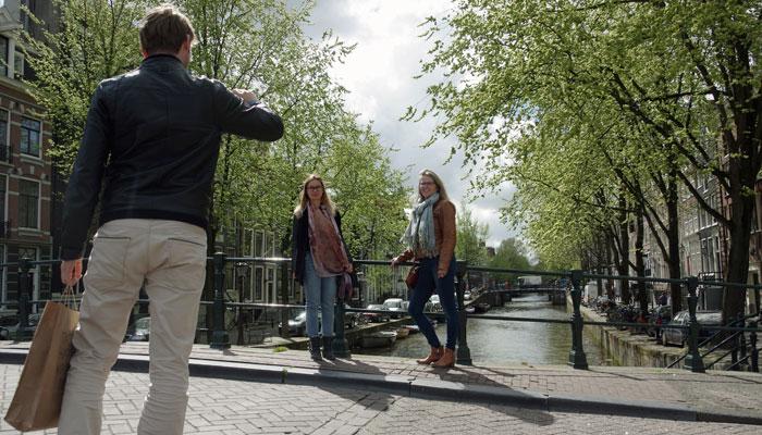 Zwei Touristen lassen sich in Amsterdam fotografieren
