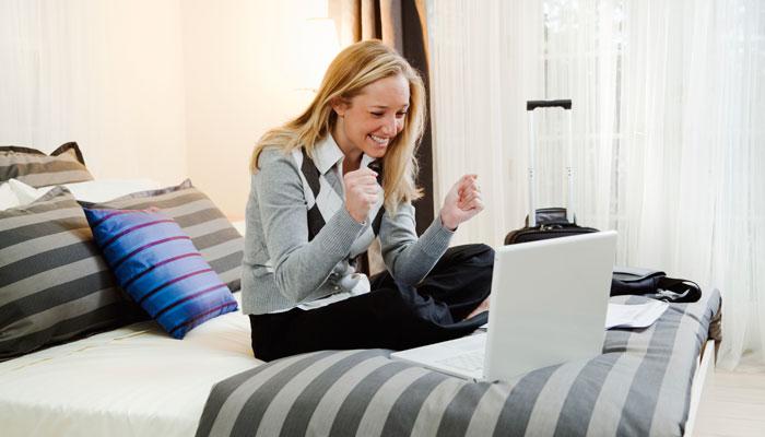 Frau mit Notebook auf Hotelbett