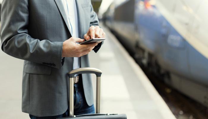 Geschäftsmann mit Handy in der Hand am Bahngleis