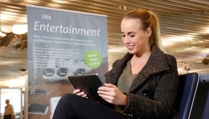 Frau mit Tablet testet das FRA Entertainment am Fraport