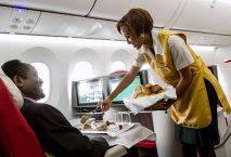 Stewardess reicht einem Passagier der Business-Class Gebäck