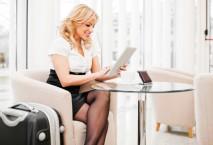 Dame am Flughafen sitzt in einem Sessel und liest