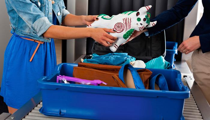 Dame an Gepäckkontrolle des Flughafen, in ihrer Hand eine Statue
