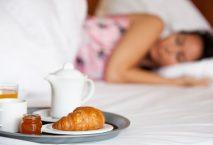 Frau liegt schlafend im Bett, im Vordergrund ein Gedeck mit Frühstück