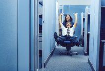 Mann lässt sich im Bürostuhl über den Gang fahren