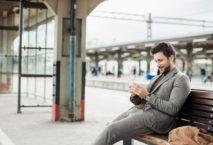 Junger Geschäftsreisender mit Smartphone am Bahnsteig