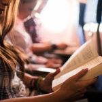 Frau liest ein Buch im Flugzeug