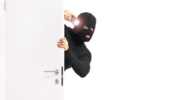 Mann mit schwarzer Maske und Taschenlampe