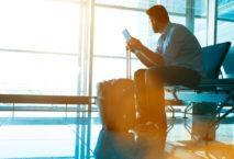 Geschäftsreisender mit Tablet und Trolley am Flughafen