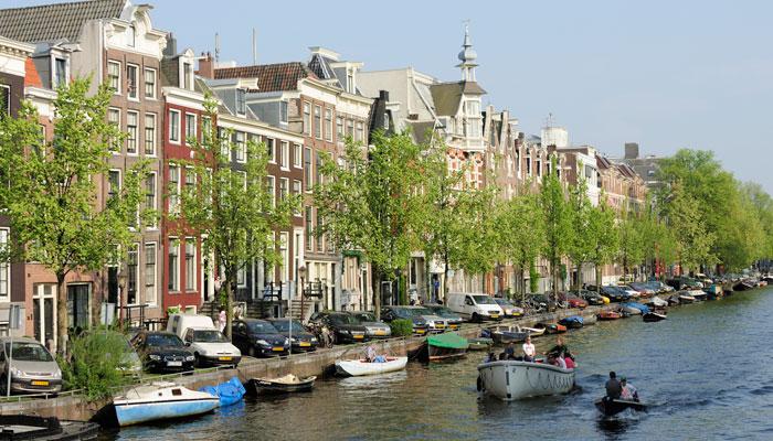 Autos parken vor Gracht in Amsterdam
