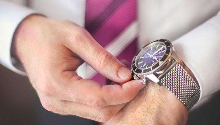 Geschäftsmann stellt seine Armbanduhr um