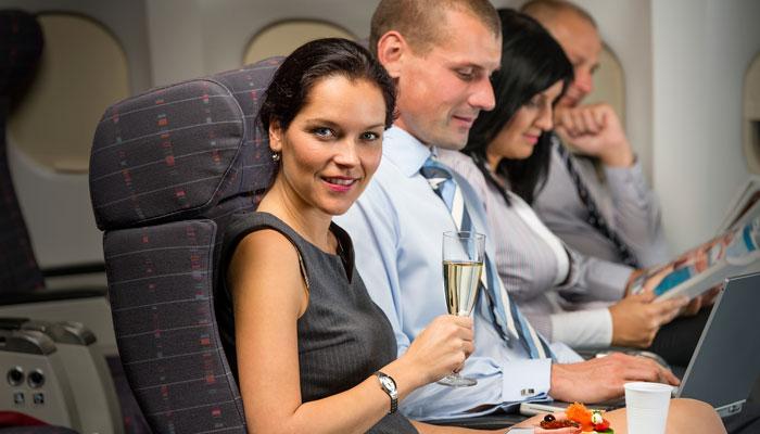 Frau mit Sektglas im Flugzeug