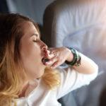 Gähnende Frau im Flugzeug