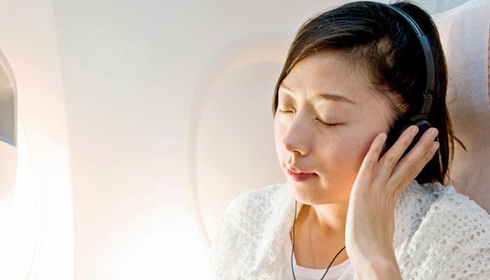 Asiatin mit Kopfhörern im Flugzeug