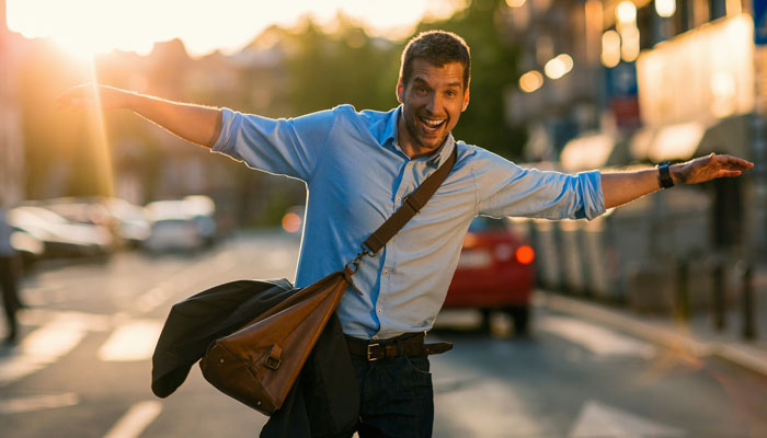 Mann mit freudig ausgebreiteten Armen auf abendlicher Straße