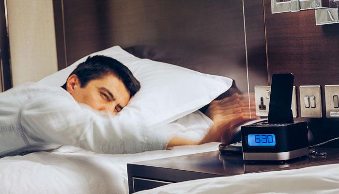 Mann im Hotelbett schlägt auf Wecker ein
