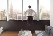 Mann steht im Hotelzimmer vor Skyline von New York