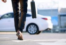 Geschäftsmann mit Aktenkoffer geht zu seinem Fahrzeug