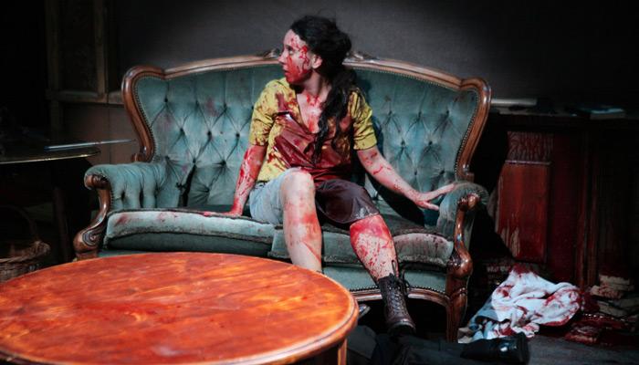 Blutüberströmte Frau sitzt auf einem alten Sofa