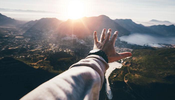 Mann streckt Hand aus vor Kapstadt-Panorama