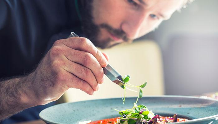 Koch richtet Teller mit Pinzette an
