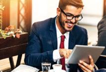 Lachender Geschäftsmann surft auf Tablet