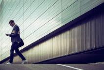 Geschäftsmann geht mit Smartphone in der Hand über Straße